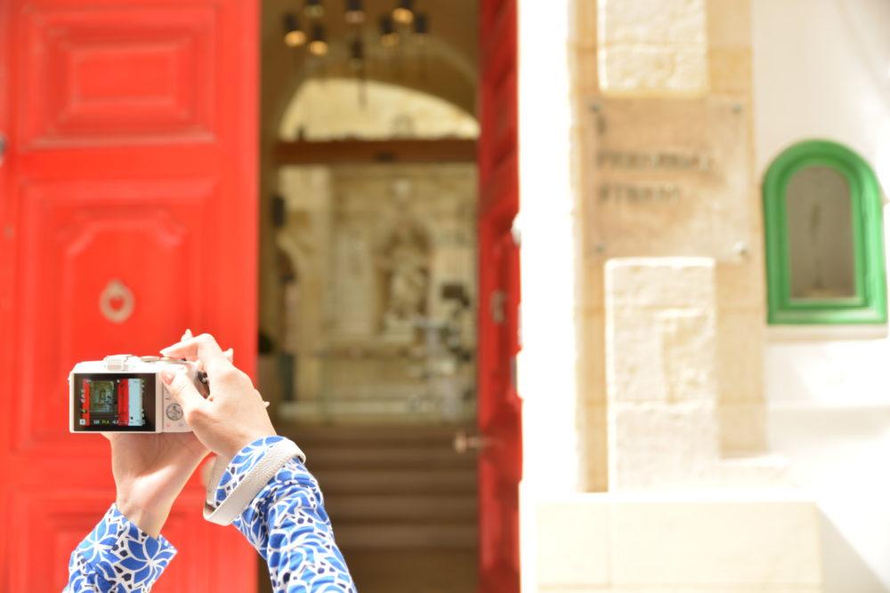 マルタ島の建物前でカメラを構える