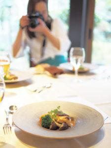 レストランで料理を写真に撮る女性